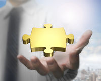 Man hand showing golden puzzle piece Stock Photos
