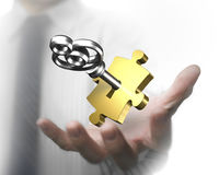 Man hand showing golden puzzle piece with silver key. Man`s hand showing one golden puzzle piece with silver key Royalty Free Stock Image