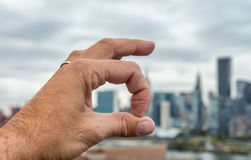 Man hand showing ok sign with city background. Success and busin Stock Images