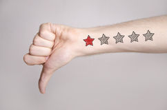 Man hand showing thumbs down and one star rating stock photos