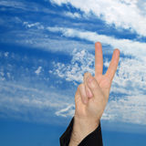 Man hand showing the victory sign on blue sky background. Royalty Free Stock Photos
