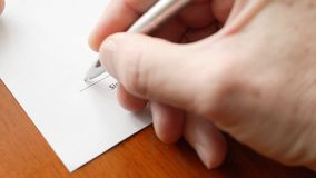 Man hand signs a paper document with ballpoint pen. Signature is fake. stock video footage