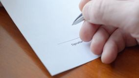 Man hand signs a paper document. Signature is fake. stock footage