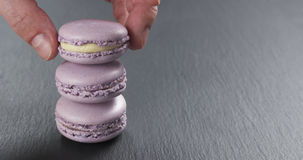 Man hand stacking lavender macarons on slate board. Man hand stacking lavender strawberry macarons on slate board, 4k photo Royalty Free Stock Photos