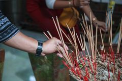 Man hand sticks burning incense in incense pot in Buddhist Temple. Buddhism, Asian traditional religious ceremony, Rituals, Making. A wish, Meditation, Praying royalty free stock images