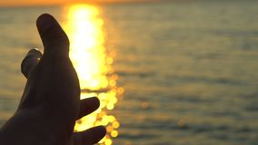 Man hand at sunset on sea, ocean beach. A man`s hand in sun`s rays on background sea water in nature. Glare of evening