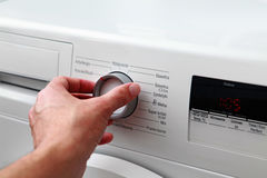Man hand switches on washing machine Royalty Free Stock Photo