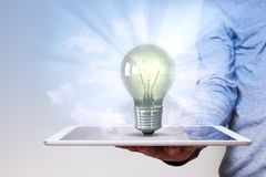 Man Hand Tablet PC Idea Bulb. Human hand with tablet pc and idea bulb Royalty Free Stock Images