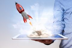 Man Hand Tablet PC Rocket. Mans hand with tablet pc and flying rocket royalty free stock images