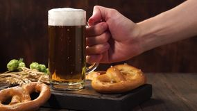 Man hand takes a glass of light beer from a dark wooden table. Man hand takes a glass mug of light beer from a dark wooden table. Lager beer with pretzels stock video footage
