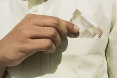 Man hand takes a new 500 indian currency note out of his pocket close up royalty free stock photo