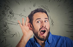 Man with hand to ear gesture and evil voices screaming blaming him Stock Photos