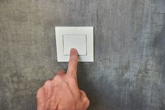 Man hand, to turn off the light, switch, front view.  stock photography