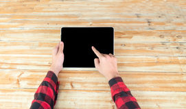 Man hand touch on a screen of laptop on a wooden table. Stock Photo