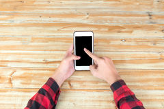 Man hand touch on a screen of mobile phone on a wooden table. Royalty Free Stock Photos