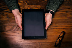 Man hand touch on a screen of mobile phone on a wooden table. Business situation. Stock Photos