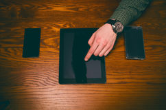 Man hand touch on a screen of mobile phone on a wooden table. Business situation. Stock Images