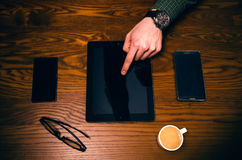 Man hand touch on a screen of mobile phone on a wooden table. Business situation. Royalty Free Stock Photos