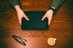 Man hand touch on a screen of mobile phone on a wooden table. Business situation. Royalty Free Stock Images