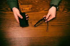 Man hand touch on a screen of mobile phone on a wooden table. Business situation. Royalty Free Stock Photo