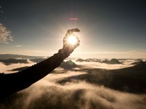 Man hand touch Sun. Misty daybreak in a beautiful hills. Royalty Free Stock Photography