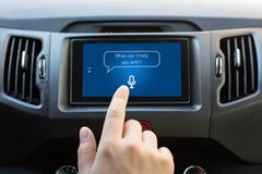 Man hand touching to multimedia system with app personal assistant. On screen in car stock image