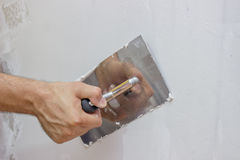 Man hand with trowel plastering a wall Royalty Free Stock Photo