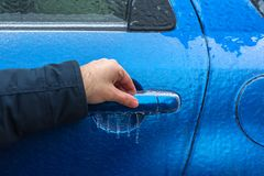 Man hand trying to open freezing car door handle, Hand on Car`s door handle after a freezing rain. Man hand trying to open freezing car door handle - Hand on Car royalty free stock photos