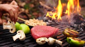 Man hand turning over fresh cut vegetables big piece of beef steak pink meat on grill pan in forest camp fire flame. Man hand turning over fresh cut vegetables stock video