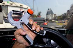 Man hand using a hand-held exercise machine in during a traffic. Jam, Man hand is exercising by hand-held machine Royalty Free Stock Photos