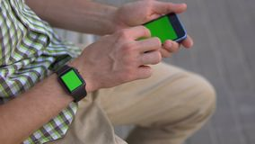 Man hand using his gadgets smart watch, smartphone sitting on bench green screen stock video