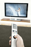 Man Hand Using Remote Control. Man's hand holding a tv remote control, pressing a button while pointing at a flat screen tv Royalty Free Stock Photo