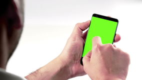 Man hand using a smart phone with chroma key on white background behind view, green screen. Lifestyle communication with smartphone technology concept stock video footage