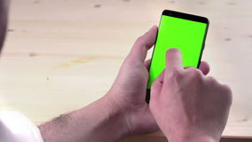 Man hand using a smart phone with chroma key on wood background, green screen, lifestyle communication stock footage