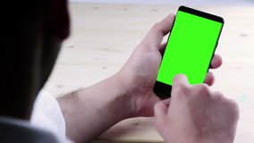 Man hand using a smart phone with chroma key on wood table behind view, green screen. Lifestyle communication with smartphone technology concept stock video