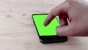 Man hand using a smart phone in the office with chroma key, green screen on wood table stock video
