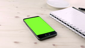 Man hand using a smart phone in the office near drink coffee with chroma key, green screen stock footage