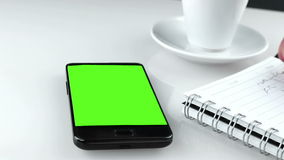 Man hand using a smart phone in the office near drink coffee with chroma key, green screen stock video footage