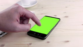 Man hand using a smart phone in the office near drink coffee with chroma key, green screen on wood table stock video footage