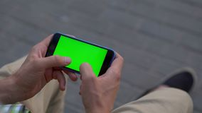 Man hand using smartphone with green screen. 4K stock footage