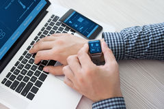 Man hand in watch with smart home computer and phone Royalty Free Stock Photos