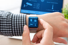 Man hand in watch with smart home and computer Royalty Free Stock Photography