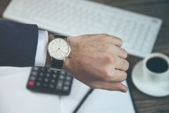 Man hand watch on working table royalty free stock photography