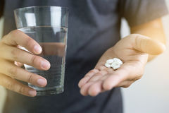 Man hand and water drug , Medicine ,Herbal supplement pill,eatin Royalty Free Stock Photography