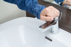 Man hand on water tap. Man hand on bathroom water tap with running water Stock Image