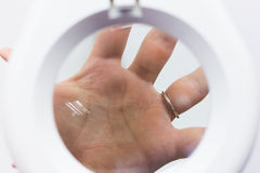 Man hand with wedding ring under the loupe Stock Photo