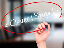 Man Hand writing Clever - Stupid with black marker on visual scr Royalty Free Stock Image