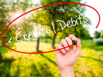 Man Hand writing Credits - Debits with black marker on visual sc Stock Photo