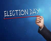 Man hand writing a 'ELECTION DAY' with gold marker. On visual screen Stock Photo