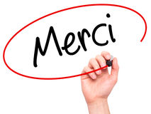 Man Hand writing Merci (Thank You In French) with black marker. On visual screen. on background. Business, technology, internet concept. Stock Photo royalty free stock photos